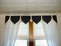 Heraldic pelmet with unlined curtains.