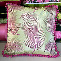 Cushion cover trimmed with pom poms.
