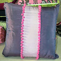 Cushion  cover with contrast and pom poms.